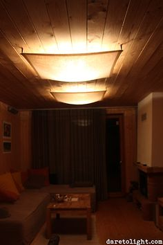 A fluorescent light is hidden behind a transparent canvas veil in a ceiling of a cottage to prevent glare and to soften the light.