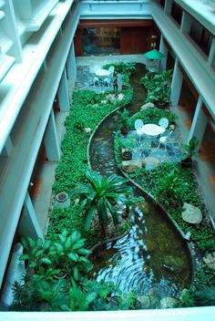 Not many people have the space for this kind of interior landscaping, but it really does look stunning! Lit by skylights, a stream with freely swimming koi fish cuts through shrubs and quaint al fresco-style dining areas.