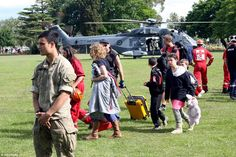 On the move: Evacuees from Kaikoura walk away from the New Zealand Air Force helicopter th...