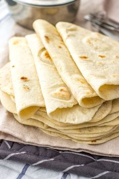 A stack of flour tortillas made from scratch, with measuring cups and spoons in the background.