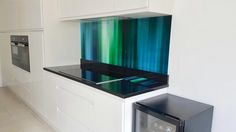 Beautiful blue and green printed glass splashback with matching worktop saver. Richard Osbourne's 'Kinetic Abstracts' bringing fabulous colour into the kitchen.