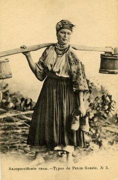 A woman in traditional Ukrainian clothes carrying water