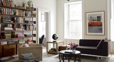 A light fixture by David Weeks in the sitting room; the sofa and cocktail table are by B&B Italia, the photograph is by Ilisa Katz Rissman, and the shelving is by Atlas Industries. (Styled by Martin Bourne; Photography by William Waldron)