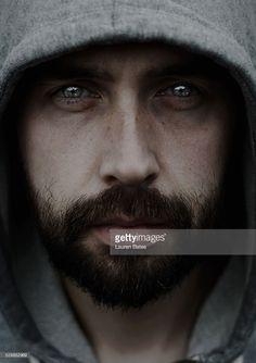 parlayan gözlerle kapüşonlu üst sakallı adam karanlık portre.