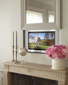 A TV over the living room mantel; an antiqued mirror lifts to reveal it.