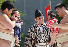 .sumo wrestling students hold babies as they try to make them cry during the crying sumo competition at sensoji temple in tokyo, japan. the first baby to cry wins the competition.