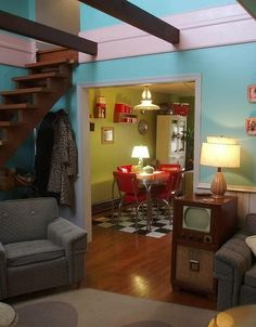 Checkered floors, spiced chartreuse walls, red diner-esque chair and table set,  1950's television.. love.