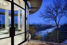 This stunning clifftop contemporary in Austin has wrap-around porches, walls of glass, high ceilings, floor-to-ceiling drapes, modern lounge furniture, a deep overhang and metal railings.