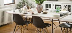 like the table and chairs. the black version of these chairs is a great idea for hiding daily wear and tear. with this minimalist design, a little green cozies up the space.