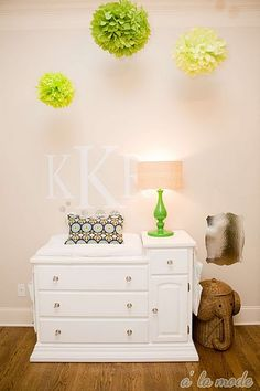 Adorable gender neutral nursery design with soft tan walls paint color, vintage changing table, green lamp, woven elephant hamper, monogrammed wall stickers and green pom poms. White Nursery, Nursery Room, Girl Nursery, Child's Room, Kids Bedroom, Nursery Decor, Bedroom Ideas, Modern Girls Rooms, Little Girl Rooms