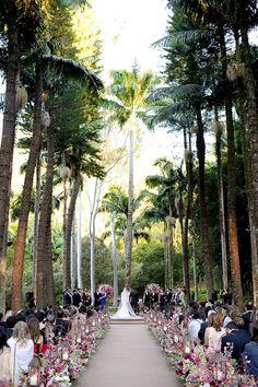 Caminho do altar: decoração com flores e velas para casamento ao ar livre.