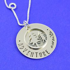 """This sterling silver necklace is stamped with """"adventure awaits"""" and topped with…"""