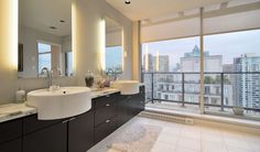 It's common for contemporary bathrooms with large windows to opt for subtle artificial lighting