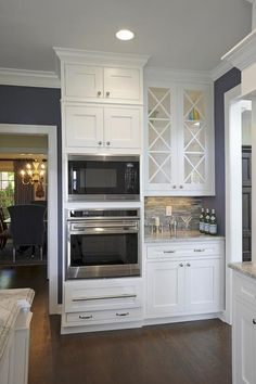 White glass doors above wet bar with crystal, bar glasses, etc.
