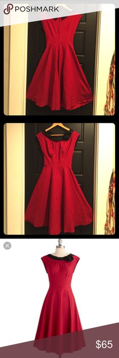 Vintage inspired dress. Vintage 50s inspired dress. Beautiful red color with black satin (satin-like?) trim and flower embellishment on collar. Fit and flare. Perfect for Christmas parties, a night out, or a photo shoot. Worn only twice. Dry clean only. Made in the USA. Body: 63% Polyester 33% Rayon 4% Spandex Modcloth Dresses Midi