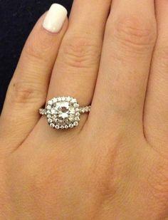 Round diamond set in a platinum and pave diamond cushion halo