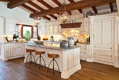 * a Clive Christian designed kitchen with state of the art appliances including a La Cornue stove, Sub Zero refrigerator, Miele dishwasher, and a large zinc top island makes this house an ideal family retreat
