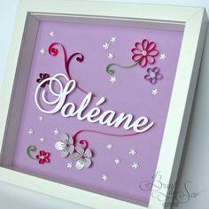 Cadeau personnalisé pour la naissance de Soléane. Quelques fleurs et arabesques avec la technique du quilling, le tout dans une gamme de violets.
