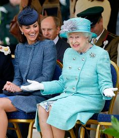 Catherine, Duchess of Cambridge (L) laughs as Britain's Queen Elizabeth II gestures as they watch part of a children's sports event on their visit to Vernon Park in Nottingham, central England, on June 13, 2012.