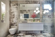 Simply Bathroom Solutions designed this bathroom in Balwyn North. We used unique screen printed tiles with a wall hung vanity and creative feature lighting to create a spectacular bathroom. #bathroom #tiles #renovation #design #bathroomdesign