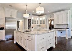 white kitchen cabinets, marble island, dark hardwood floors