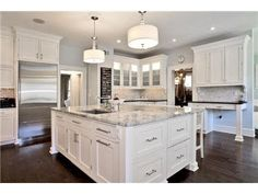 white kitchen cabinets, marble island, dark hardwood floors