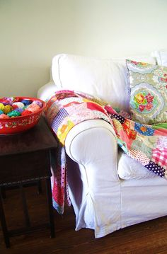 white, slipcovered sofa with bright, colorful quit and pillows