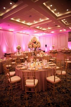love the color combination - gold/champagne chairs, blush tablecloth, white and blush flowers but with purple uplighting
