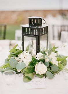 black lantern white roses and green eucalyptus wedding centerpiece