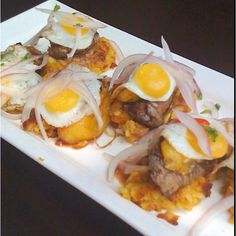Tacu Tacu is a mixture of beans and rice, fried, and topped with breaded and pan-fried steak and an onion salsa. Peru.