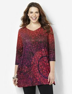 Our signature L'Attitude tunics are extra-long for complete coverage and look great paired over leggings and slim-leg pants. This V-neck tunic features a fantastical flourishing print in rich shades. Silky, lightweight style shines with colorful rhinestones at the chest. Complete with three-quarter sleeves and side slits at the hem. Catherines tops are designed for the plus size woman to guarantee a flattering fit. catherines.com
