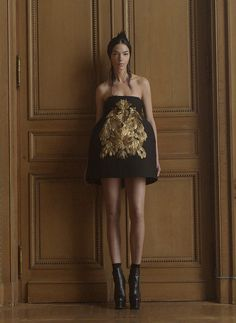 LOOK 5: Black structured wool strapless ballerina mini-dress with bell skirt and hand painted gold leaf feather appliqué