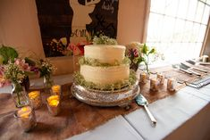 """Simple wedding cake trimmed with baby's breath sits on a silver antique cake stand from Flowers, tea lights, and a deer sign that says, """"I love you dearly. Barbecue Wedding, Deer Signs, Baby's Breath, Tea Lights, Wedding Cakes, Table Decorations, Antique, Simple, Flowers"""