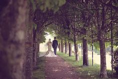 Wedding couple walk down tree tunnel at Rhinefield House Wedding.Photography by one thousand words wedding photographers
