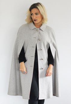 Gorgeous 1970s grey cape. Love the bright red internals. Super chic. A really gorgeous quality piece. Found in Italy and in excellent condition. One size. Model is a size 8 and 5ft 3. A little big on our model, but can generally fit anyone depending on how oversized you like to wear it. See a move of this piece in action here! https://www.facebook.com/welovevintageboutique/