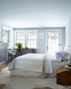 Beautiful and airy light blue bedroom featuring large windows and a fluffy white bed