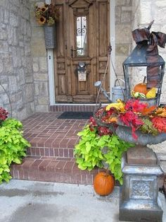 "The entry to our home on Clarion Lakes Way.  You can't go wrong with cast iron urns leading up to your ""castle"".  I change mine seasonally using real and faux greenery, leaves, pumpkins and gourds in the fall.  As Christmas approaches I change out the fall decor and add giant sugar pinecones, Christmas greens and giant, colorful balls."
