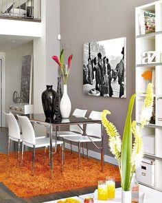 Comedor con sillas blancas sobre alfombra naranja