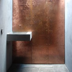 A copper shower wall contrasts with the concrete sink in the bathroom of this garden studio in English countryside, echoing the cladding used on the outside of this building.