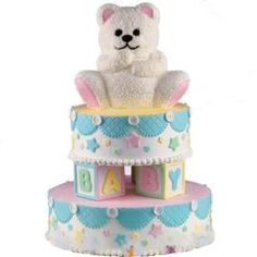 Teddy's Ready to Play! This colorfully stacked cake is the perfect centerpiece for baby showers or first birthday celebrations.