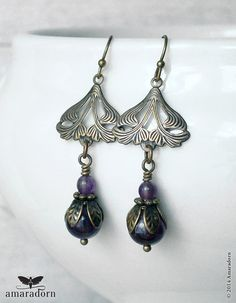 Art Nouveau inspired floral antiqued brass earrings with dark purple amethyst gemstone beads, leafy bead caps and bronze plated spacers. Attached to