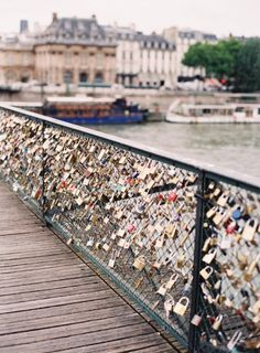 Locks of love in Paris..I want to go here with my husband one day. You are supposed to put a lock with you and your gf/bf or husband/wife names on the fence and then throw the key in the river