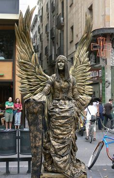 Barcelona, Spain, is a popular destination where visitors can stroll the Ramblas, see the Picasso Museum and Gaudi architecture, and enjoy tapas bars. Barcelona Street, Barcelona Travel, Barcelona Las Ramblas, Living Statue, Street Magic, World Street, Angel Images, Street Performance, Angels Among Us