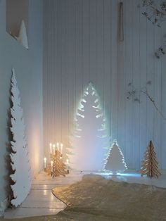 Cardboard cutout of a Christmas tree - paint it white and add a string of white lights behind it. by joeyd