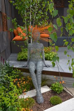 Fascinating wire sculptures with hints of orange in hair & cushions!