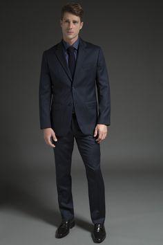 Camisa azul acetinada, gravata de tricô e costume marinho. A produção total blue é uma tendência da estação e, nesse caso, a melhor combinação de cor para os acessórios (sapato, cinto e pasta) é o marrom ou café.