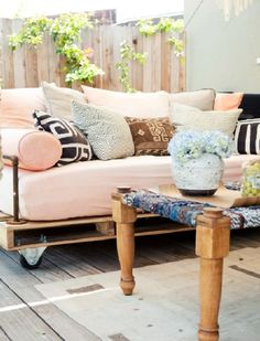 DIY pallet daybed with plumbing pipe guards to keep in big fluffy cushions