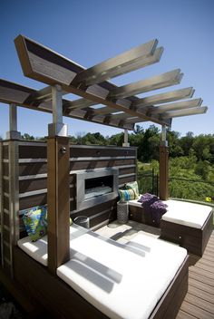 """The built-in benches surrounding this deck's fireplace are a perfect vantage point to enjoy the view.  From """"Decked Out"""" project """"The Fireplace Deck"""".  Deck Design by Paul Lafrance Design."""