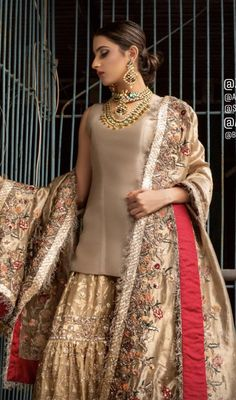 Ivory plain shirt is paired up with golden traditional gharara done with floral motifs all over. It is beautifully matched with golden dupatta with colorful embellishment. Nikkah Dress, Shadi Dresses, Pakistani Formal Dresses, Pakistani Wedding Outfits, Pakistani Dress Design, Pakistani Wedding Dresses, Indian Dresses, Indian Outfits, Pakistani Gharara