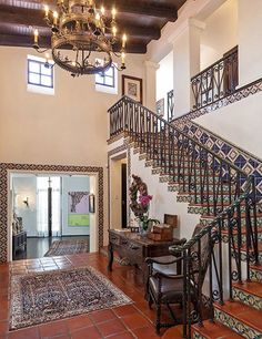 A double-height ceiling, a three-tier chandelier, and beautiful tilework create an impressive entrance area.